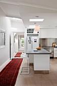 Zeitgenössische offene weisse Küche mit orientalischem Teppichläufer im Gangbereich