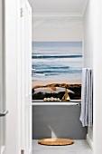 View through open door into bathroom; poster with beach and ocean motif above bathtub