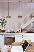 Open-plan interior with kitchen counter below retro pendant lamps & staircase with wooden balustrade