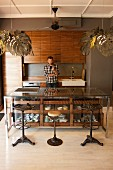 Vintage barstools at counter with glass-fronted drawers in open-plan, fitted kitchen with pendant lamps with lampshades made from stylised leaves; man behind counter