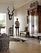 Elegant interior with antique cupboard, colourful rattan basket, zebra-skin rug and wooden floor; woman in background next to hunting trophy on wall