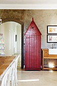 Former sentry box painted rust red in dining room against concrete-effect wall and next to arched doorway