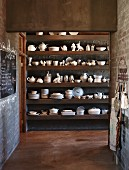 Open kitchen doorway with view of crockery on wall-mounted shelving in rustic ambiance