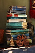 Old child's shoes and brass ornament in front of stacked books on blue trunk