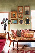 Scatter cushions with various patterns on antique bench in lounge-style room with collection of framed mirrors on green wall