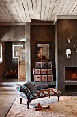 Antique chaise longue on rug in front of open fireplace and animal trophies on wall in rustic, country-house living room
