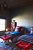 Colourful, striped bedspreads on twin beds and stools with red cushions in simple room
