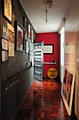 Narrow hallway with framed photos on wall painted with chalkboard paint and old mosaic parquet floor