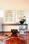 Pictures on postmodern console table behind metal chair on old mosaic parquet floor