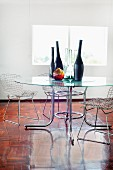 Collection of vases on glass table and Bauhaus wire chairs in minimalist ambiance