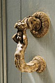Artistically hand-crafted bronze figurine as handle on wooden door