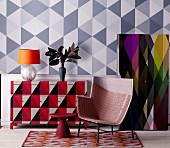 Colour scheme with geometric triangular patterns on wall, cupboard and chest of drawers behind armchair and side table