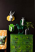 White, china animal heads on colourful shields on black wall and green horse ornament on jungle-patterned chest of drawers