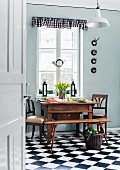Antique, Biedermeier-style table and chairs below old hunting horn hanging in kitchen window; black and white gingham pelmet and chequered floor