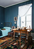 Blue striped wallpaper and Biedermeier desk below window in guest room with single bed