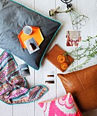 Still-life arrangement of cushions, photos and various home accessories on white-painted wooden surface