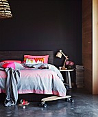 Skateboard on floor in front of double bed with headboard against black wall