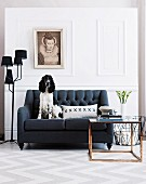 Dog sitting on black, vintage sofa next to black, multi-armed standard lamp against white, wood-panelled wall