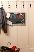 Hand-sewn, wall-mounted, denim pinboard on white-painted, wood-clad wall in hallway