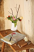 Book in handmade, embroidered fabric book jacket and vase of flowers on small, rustic wooden table