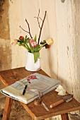 Selbstgemachter Stoffeinband mit Stickerei und Blumenstrauss auf rustikalem Holztischchen