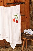 Tablecloth with embroidered floral motif hanging on washing line