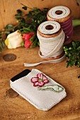Embroidered mobile phone pouch and wooden reels of velvet ribbon on rustic wooden surface