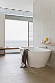 Free-standing, designer bathtub in purist bathroom in front of open glass wall with sea view