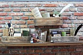 Collection of objet on small shelves made from pallet remnants mounted on brick wall