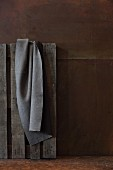 Grey felt blanket hanging on pallet against corten steel wall
