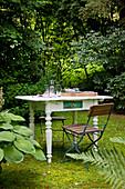 Klappbare Gartenstühle und weiss lackierter Tisch mit gedrechselten Beinen im Shabby Stil im Garten
