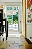 Bugholzhocker an schwarzer Theke in Küche mit Kalksteinfliesen; Blick durch Fenstertür auf die Terrasse