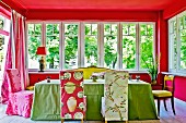 Colourful dining area in extension with bright, patterned loose chair covers and green tablecloth combined with red-painted walls