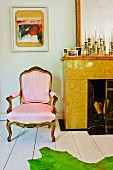 Contemporary artwork above Rococo armchair with pale pink upholstery next to marble fireplace with collection of old candlesticks