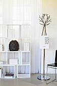 White shelving unit in front of window next to metal coat rack