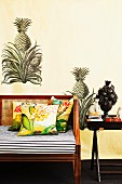 Partially visible bench with seat cushion and scatter cushions next to tray table against wall with painted pineapple motif