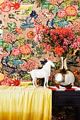 White horse ornament next to flowers in chrome vase against colourful, patterned wallpaper