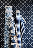 Bolts of fabrics in various patterns of blue and white against wallpaper with pattern of blue and white lozenges