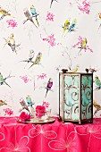 Decorative candle lantern on pink cloth against wall with whimsical, budgerigar-patterned wallpaper