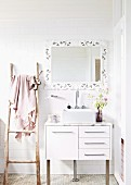 Sink with base cabinet against white tiled wall and below framed mirror next to rustic wooden ladder used as towel rack