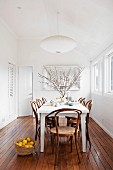 White table and Thonet chairs on elegant wooden floor in white, minimalist dining room