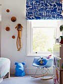 Blue accents in child's bedroom with patterned Roman blind, dog figure and classic rocking chair; striped sock monkey on wall