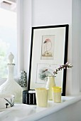 Various ceramic beakers and flowering twig in vase next to framed drawings on window sill