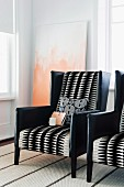 Elegant armchairs upholstered in black leather and geometric, black and white patterned fabric