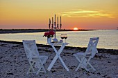 Romantic candlelight dinner on beach at sunset