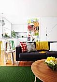 Mit bunten Kinderbildern, gemusterten Kissen und Vintage Hockern dekorierter Wohnraum mit offener, schlicht weisser Küche