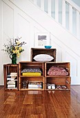 Vintage wooden crates used as shelving for books, shoes and cushions in spacious hallway of 20's house with white, classic wooden staircase