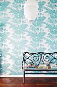 Alte Jugendstil Bank aus Bugholz mit Geflechtsitz und weisser Deckenlampion vor Wandtapete mit floralem Muster