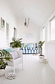 White, maritime-style conservatory with striped sofa, wicker chair and potted plants