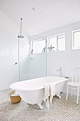 Free-standing bathtub and white-painted Thonet chair next to floor-level rainfall shower with glass partition